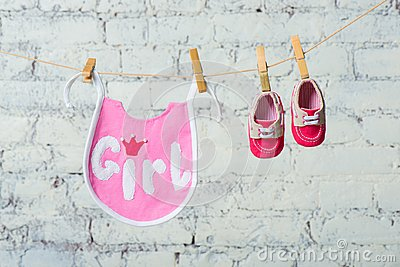 Children`s toddler pink saliva and red shoes on a rope against a white brick wall.