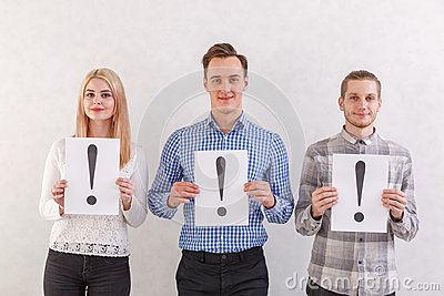 Two guys and a girl with light smiles are standing next to keep the sheets with exclamation marks on a gray background
