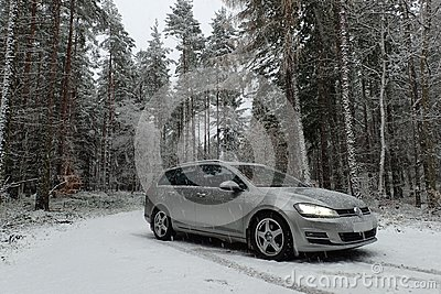Winter scene of Volkswagen Golf MK7 variant in snowy pine tree forest