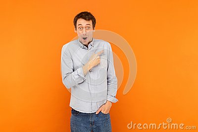 Amazement man pointing finger at copy space, open mouth and look