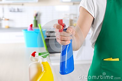 Cleaning service worker holding bottle with cleanser,