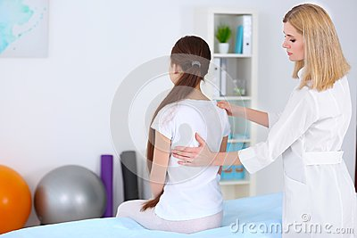 Incorrect posture concept. Physiotherapist  examining and correcting girl`s back