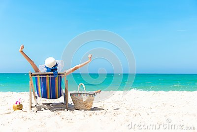 Summer Vacation. Beautiful young asian woman relaxing and happy on beach chair with cocktail coconut juice