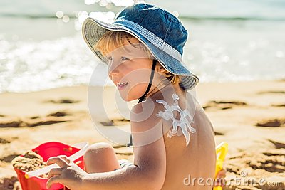 The sun drawing sunscreen ,suntan lotion on baby boy back. Caucasian child is sitting with plastic container of sunscreen and toys