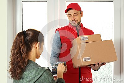 Young woman paying for parcels received from  courier