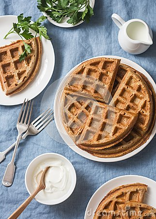 Whole wheat savory breakfast viennese waffles, cream and milk on blue background