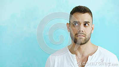 Portrait of young handsome man grimacing into camera and show different emotions on blue background