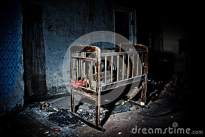 Old creepy eerie wooden baby crib in abandoned house. Horror concept