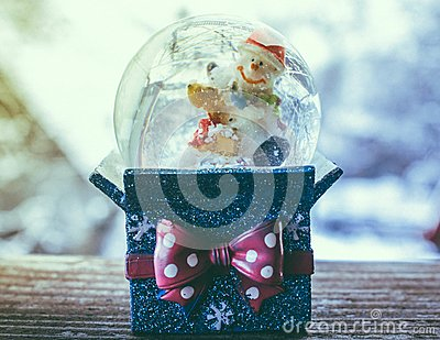 Christmas Snow globe present Snowflake with Snowfall and snowman toy on Blue Background