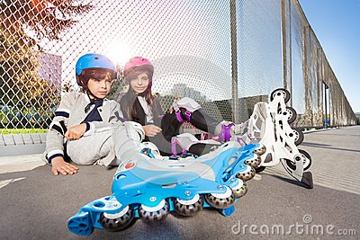 Happy inline-skaters sitting on the floor outdoors