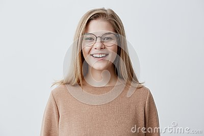Headshot of pleasant-looking young Caucasian woman wearing eyeglasses with broad smile showing her straight white teeth