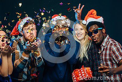 Friends at New Year`s party, wearing santa hats, dancing and blowing confetti