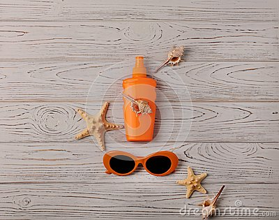 Glasses of orange color and sunscreen on a wooden background.