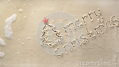 Holiday background - merry Christmas and tree with starfish drawn on a sandy beach