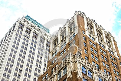 Angled view up at ornate old tall office buildings from street level