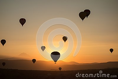 Hot air balloons in the sky during sunrise. Flying over the valley at Cappadocia, Anatolia, Turkey. Volcanic mountains in Goreme n