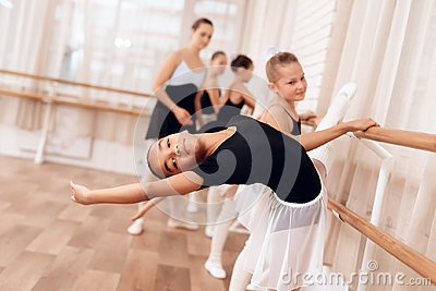 The young ballerina makes a dance movement with her hands during a class at a ballet school.