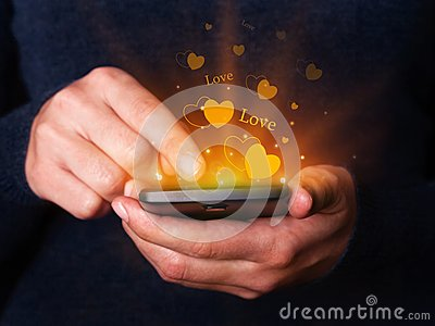 Woman hands holding and using smartphone mobile or cell phone for texting or messaging for Valentines Day.