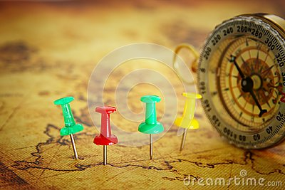 Image of pins attached to map, showing location or travel destination over old map next to vintage compass. selective focus.