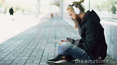 Young bearded hipster man with headphones sitting on road and using smartphone for listen to music and internet surfing