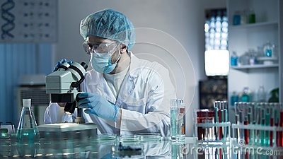 Lab assistant studying samples to detect pathologies, quality medical research