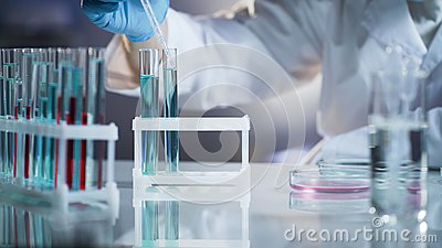 Scientist taking drops of liquids to check chemical reaction at research lab