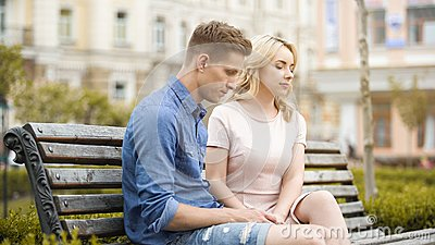 Couple feeling awkward, sitting on bench in silence, crisis in relationship