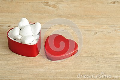 A red heart shape tin filled with hearts