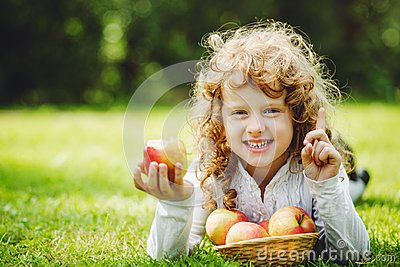 Little girl is eating apple and smiling showing white teeth.