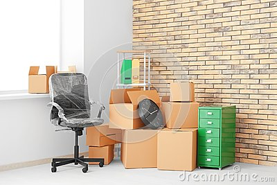 Office move concept. Carton boxes and furniture