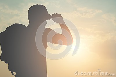 Silhouette of a tourist backpacking a man wearing a cap is going out to the world