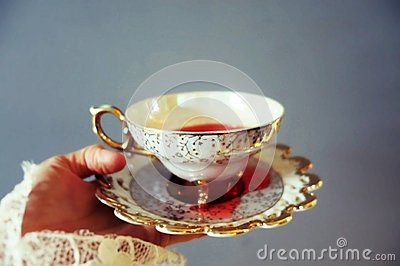 Woman`s hand holding delicate tea cup and saucier full of red liquid