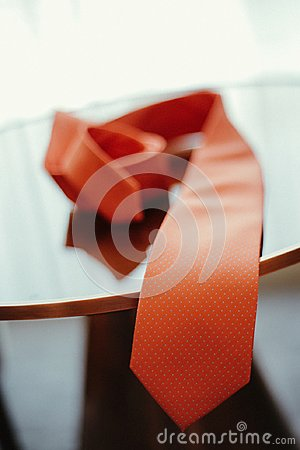 Red tie on wooden table, marriage prepration, betrothal, formal tie