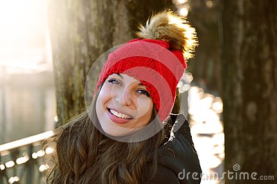 Young Smile winter young woman portrait. Beauty joywoman looking to the side outdoor in a sunny day with flare and city background