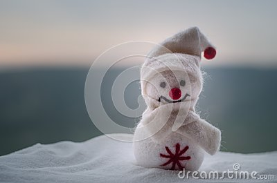 New Year Christmas concept. The snowman stands on snow with blurred nature background. White snowman surrounded by Christmas trees