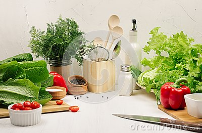 Healthy vegetarian ingredients for spring fresh green salad and kitchenware in white elegant kitchen interior.