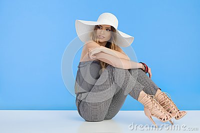 Beautiful Fashion Model In Jumpsuit And White Sun Hat Is Sitting And Looking Away Over Shoulder