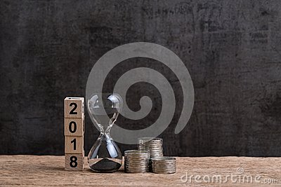 Year 2018 financial or investment time or goals concept with hourglass or sandglass and stack of coins and cube block with number