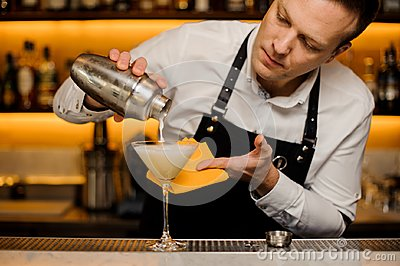 Bartender pouring a fresh alcoholic drink into the cocktail glass