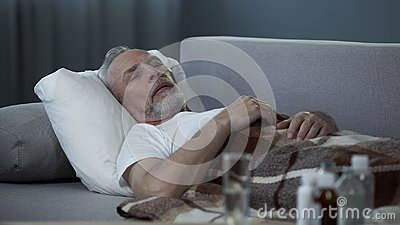 Male in his 60s sleeping in bed at home, pills and fluids standing on the table