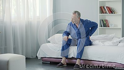 Senior male suffering sharp back pain, sick person getting up from bed, morning