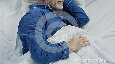 Old man sleeping in bed in the morning, recovery time and healthy sleep
