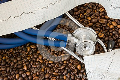 Coffee or caffeine and heart arrhythmias irregular heartbeat. Stethoscope and ECG tape on background of coffee beans. Effect and