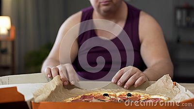 Obese man looking at fatty pizza on table, junk food addiction, overeating