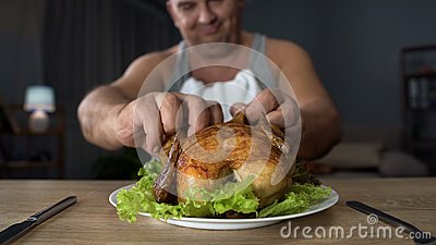 Bad-mannered overweight man tearing piece of chicken with hands, overeating