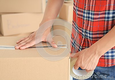 Young man packing box