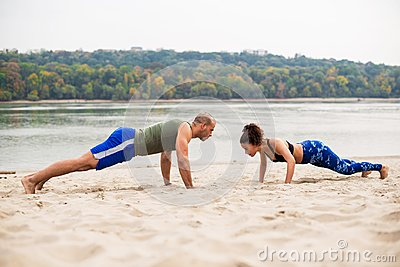 Heterosexual couple work out on the beach