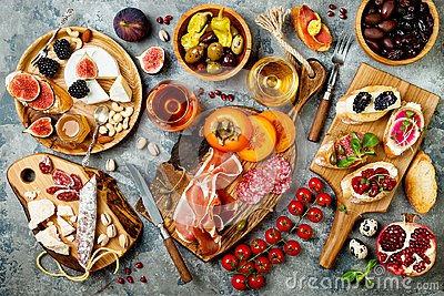 Appetizers table with italian antipasti snacks and wine in glasses. Brushetta or authentic traditional spanish tapas set