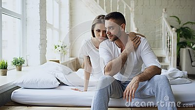 Depressed yong man sitting in bed having stressed while his girlfriend come and embrace him and kiss in bedroom at home