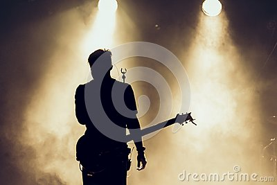 Rock band performs on stage. Guitarist plays solo. silhouette of guitar player in action on stage in front of concert crowd. Close